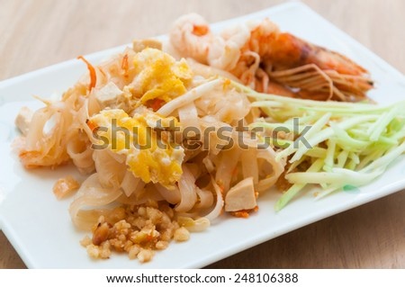 Seafood pad Thai dish of stir fried rice noodles on a square white plate - stock photo
