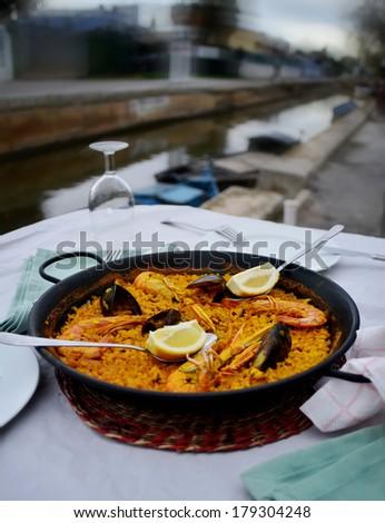 Seafood Paella in black pan -traditional spanish rice dish - stock photo
