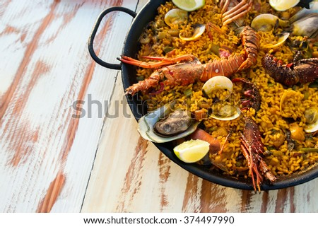 Seafood paella on the wooden table close-up - stock photo