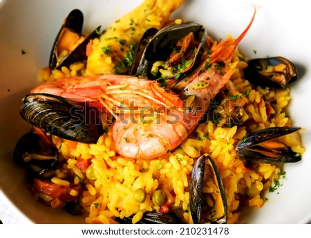 Seafood paella with chicken casserole and chorizo sausage in rustic restaurant.