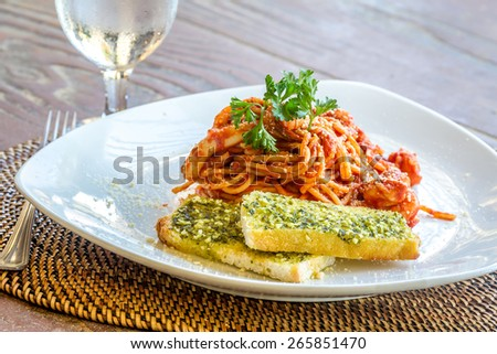 seafood pasta in tomato sauce served in a small outdoor restaurant, meal time - stock photo