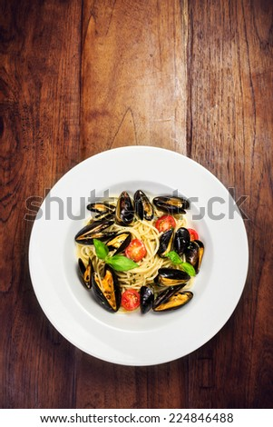 Seafood  Pasta with mussels, cherry tomato  and basil in white plate on wooden table, top view - stock photo