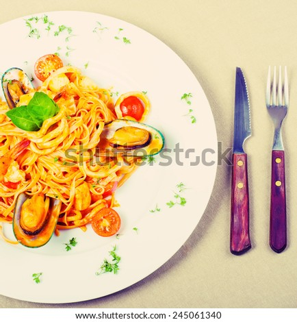seafood pasta with prawns, mussel and scallops on a white plate, filtered. - stock photo