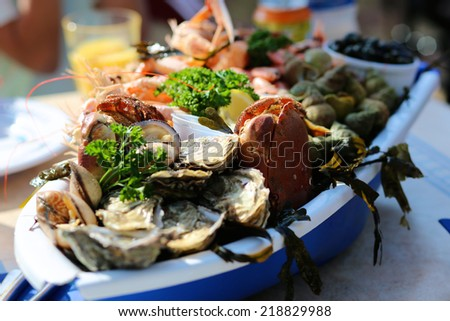 Seafood plate with crab, prawns, shrimps and oysters served in traditional beach restaurant at North Sea, France or Belgium - stock photo