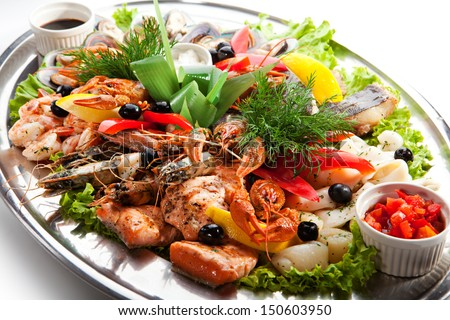 Seafood - Prawns, Squids, Scallops, Mussels, Fillet of Salmon, Crawfish, Greens and Lemon - stock photo
