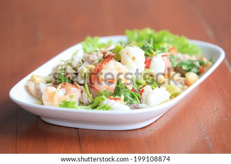 Seafood salad on wooden background - stock photo