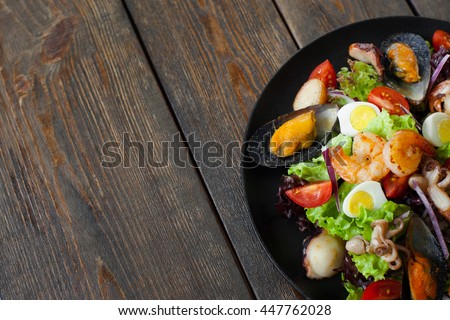 Seafood salad plate on wood half image copyspace. Portion of salad with grilled shrimps, mussels and octopus on side of picture on wooden background with free space - stock photo