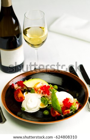 Seafood salad with red caviar and vegetables with a bottle and a glass of wine on a white tablecloth background, studio light