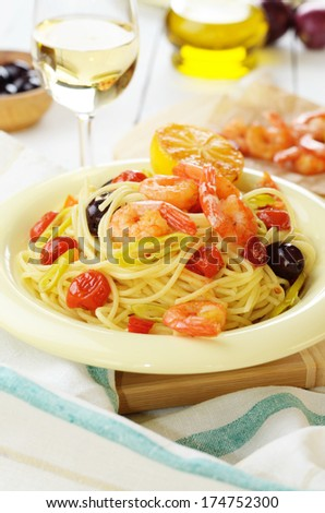 Seafood spaghetti pasta dish with shrimps and cherry tomatoes served with white wine - stock photo