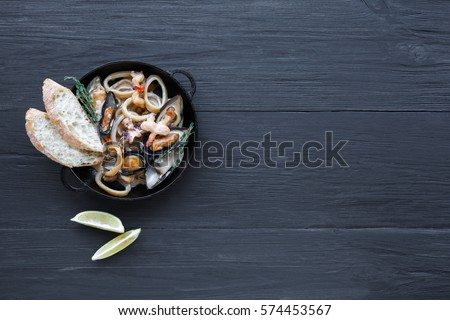 Seafood Stew in Saucepan. Authentic italian restaurant cuisine, healthy food. Oysters, shrimps, calamari in white cream with bruschetta. Bowl on dark black wood background, top view with copy space