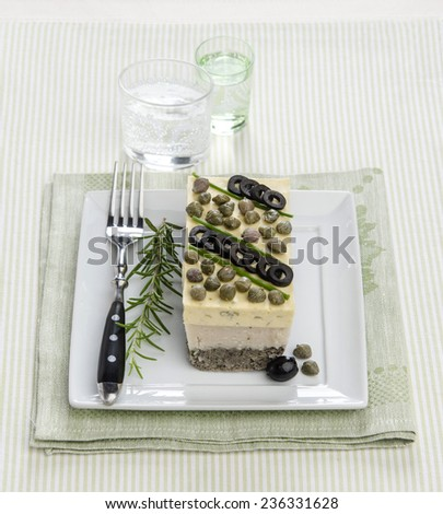 seafood terrine with capers olives with rosemary on a white square plate striped napkin - stock photo