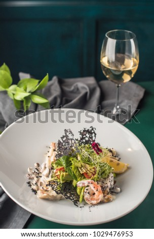 Seafood, vegetables and flowers in a white plate and glass wine close-up. Fresh food on a dark tablecloth.