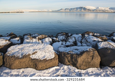 Seafront at Reykjavik at sunny winter day, city landscape with mountains, Iceland