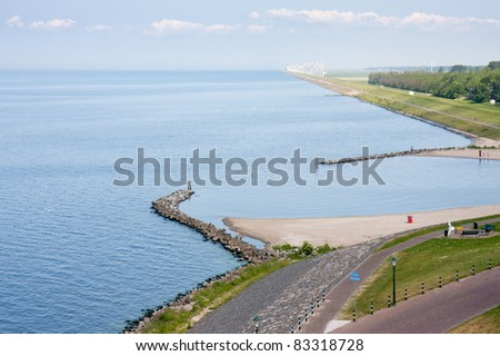 Seafront of a Dutch town with in front a big windfarm - stock photo