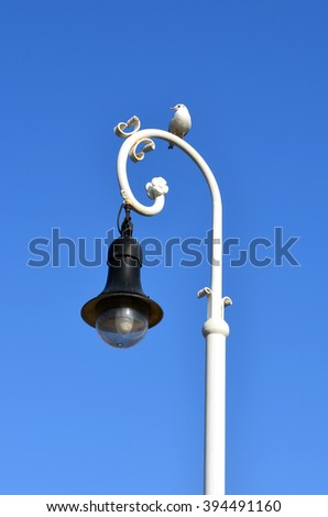 seagull standing on lamp post with clear blue sky - stock photo