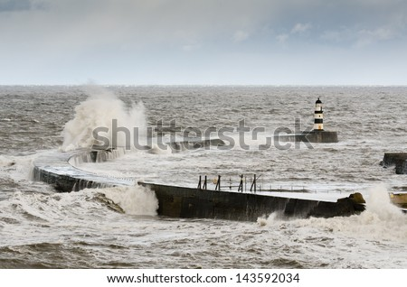 Seaham Harbour with crashing waves / Crashing waves over the north pier in a rough sea at Seaham Harbour