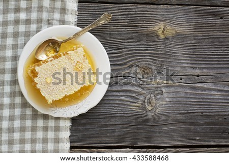 Sealed honeycomb full of fresh flower light honey on white ceramic plate with a teaspoon of German silver spoon on a rustic wooden background. Horizontal - stock photo