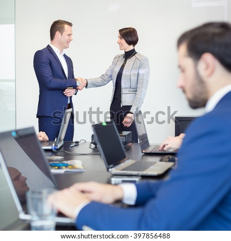 Sealing a deal. Business people shaking hands, finishing up meeting in corporate office. Businessman working on laptop in foreground. Business and entrepreneurship concept. - stock photo