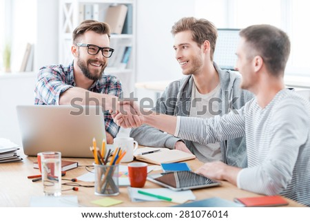 Sealing a deal. Business people shaking hands while sitting at the desk in office  - stock photo