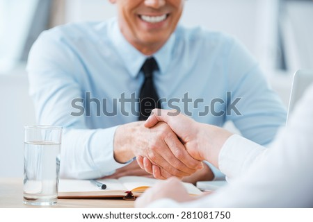 Sealing a deal. Close-up of two business people shaking hands while sitting at the working place - stock photo