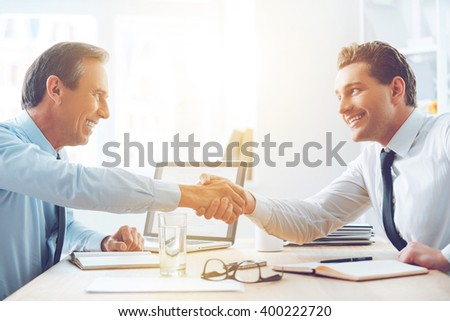 Sealing a deal. Side view of two business people shaking hands while sitting at the table in office - stock photo