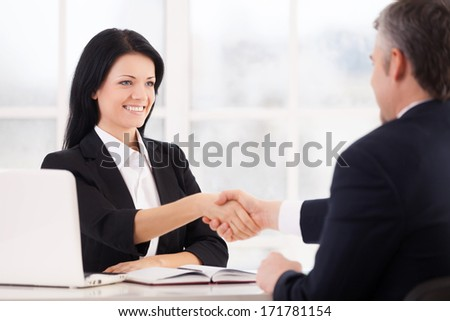 Sealing a deal. Two cheerful business people handshaking and smiling while sitting face to face at the table - stock photo