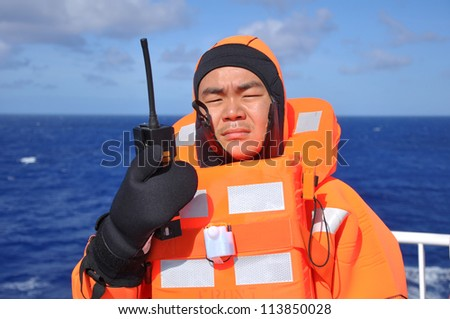 seaman in immersion suit and with portable radio during lifeboat drill on board of vessel - stock photo
