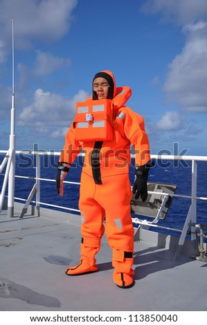 seaman in immersion suit  during lifeboat drill on board of vessel