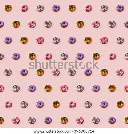 Seamless pattern with colorful glazed donuts on pink background. 4 different kinds of frosting - pink with marshmallow, yellow with chocolate, white and purple with sweet topping. - stock photo