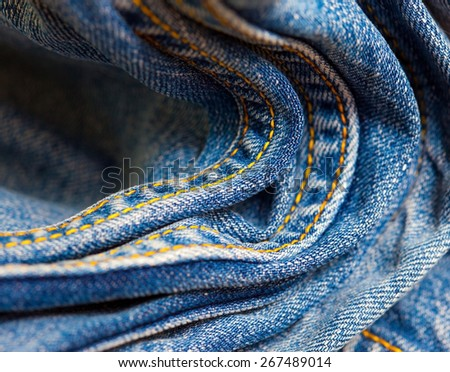 seams with yellow thread on blue jeans, close-up - stock photo