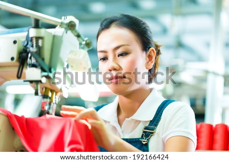 Seamstress or worker in a chinese factory sewing with a industrial sewing machine, she is very accurate - stock photo
