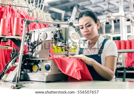 Seamstress or worker in Asian textile factory sewing with  industrial sewing machine