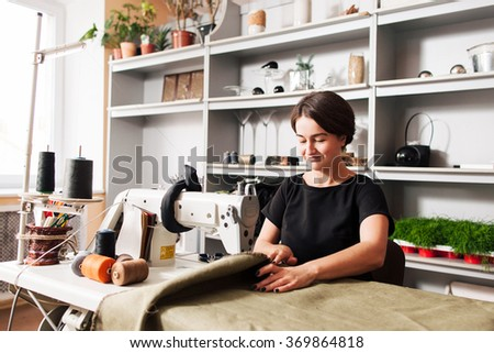 seamstress sews clothes. Workplace of tailor - sewing machine, rolls of thread, fabric, scissors. - stock photo