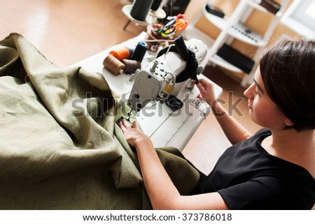 seamstress sews clothes. Workplace of tailor - sewing machine, rolls of thread, fabric, scissors. top view - stock photo