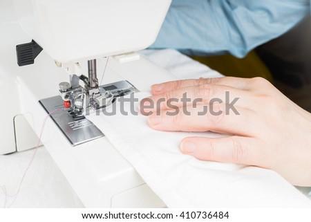 Seamstress using white sewing machine, close-up. Woman hand sewn white cloth - stock photo
