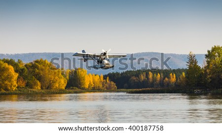 Seaplane flying over the bay near the island - stock photo