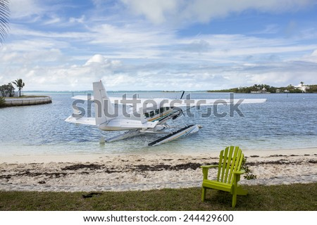 seaplane next to beach at tropical resort in bahamas - stock photo