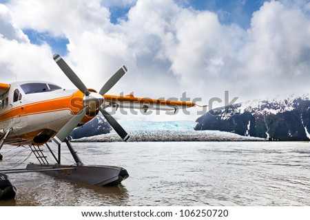 Seaplane or float plane in Alaska. The plane has landed under stormy skies near a glacier. - stock photo