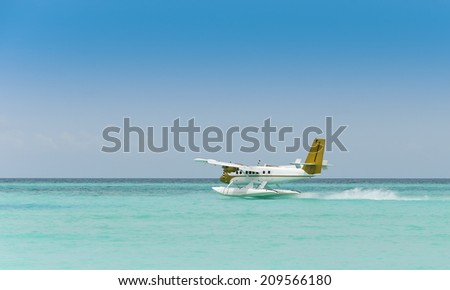 Seaplane taking off over the blue ocean of the Maldives - stock photo