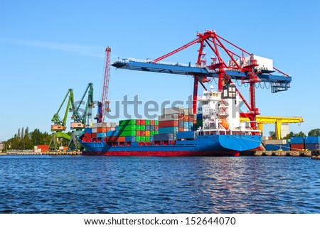 Seaport crane and huge container cargo ship ready for unloading. - stock photo