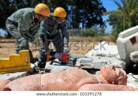 Search and rescue forces search through a fallen building for survivors during an exercise. - stock photo