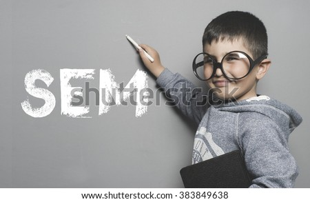 Search engine marketing, boy with glasses and funny gesture writing on the blackboard the text SEM