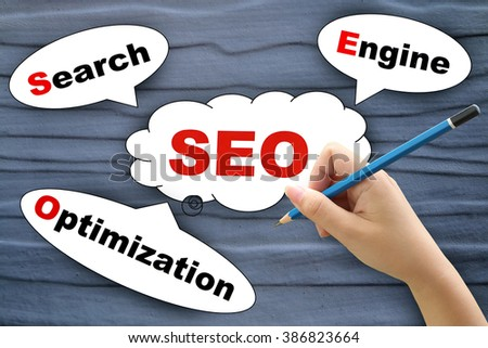 search engine optimization tag on wooden wall with hand holding pencil - stock photo