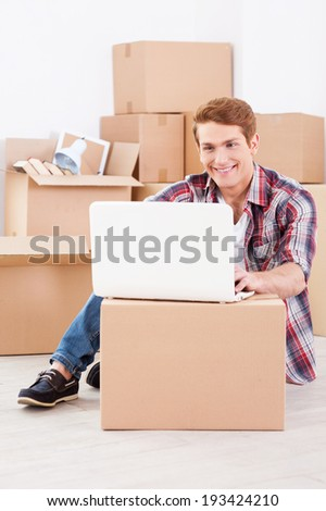 Searching a moving company in the net. Cheerful young man sitting on the floor and working on laptop while cardboard boxes laying in the background