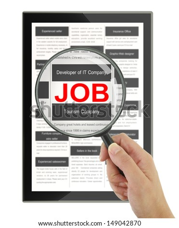 Searching for a job with a magnifying glass in a digital tablet  - stock photo