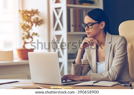Searching for new solution. Pensive young beautiful businesswoman in glasses working on laptop and keeping hand on chin while sitting at her working place - stock photo