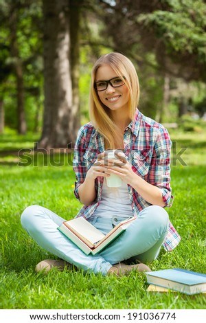 Searching inspiration outdoors. Beautiful young female student adjusting her glasses and smiling while sitting in a park with books around her