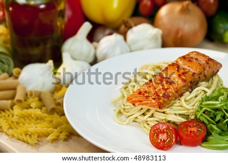 Seared chili salmon fillet with pesto spaghetti, rocket salad and cherry tomatoes out of focus in the background are vegetables dried pasta and olive oil - stock photo
