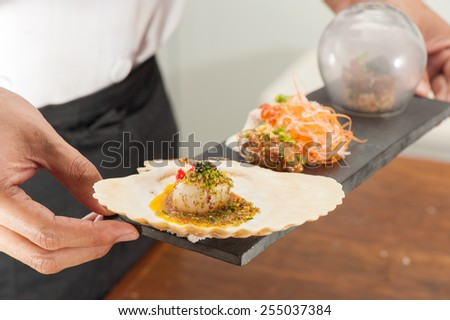 Seared scallop with parmesan crust and egg yuzu sauce, Akami tataki with ponzu foam, Aji ginger spicy, Smoked brown rice and jalapeno chili salsa topped with hamachi carpaccio and black garlic - stock photo
