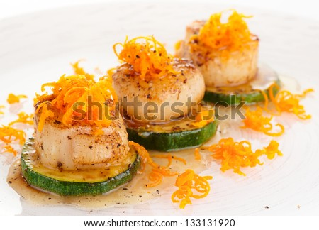 Seared scallops with citrus zest and sweet-sour sauce on plate - stock photo